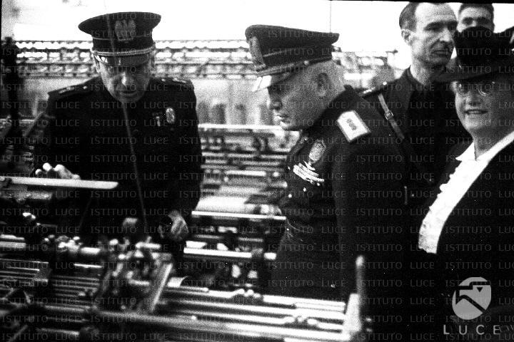 Benito Mussolini, insieme ad altri gerarchi fascisti e a Barbara Orsi Mangelli, osserva un macchinario per tessere, all'interno di un laboratorio dell'industria Orsi Mangelli